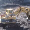 Image shows coal being loaded into trucks at a coal mine