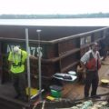 Photo of USGS and FWS scientists studying the interaction of moving barges and small fish on the Illinois Waterway.